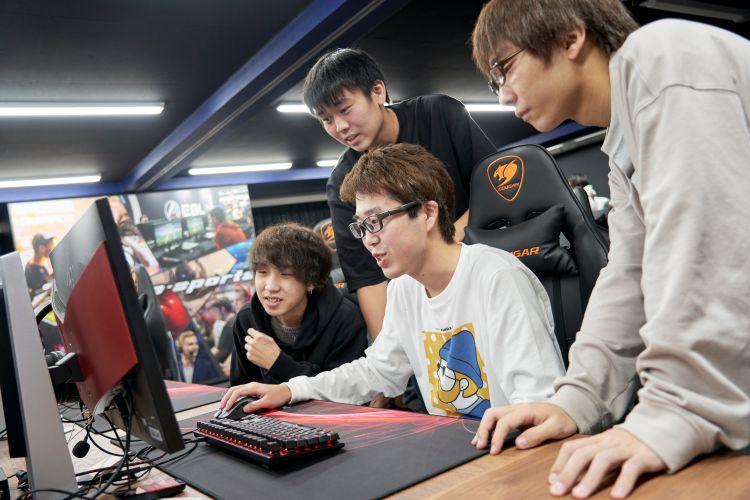 パソコンの画面を眺める学生たち