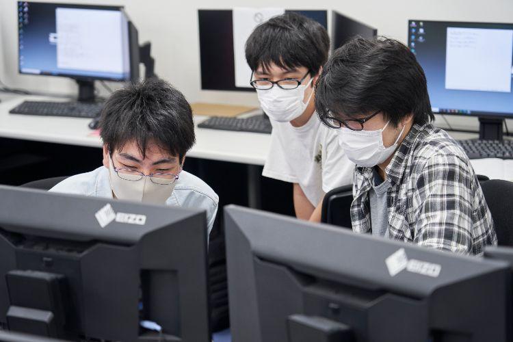 パソコンの前で話し合う学生たち