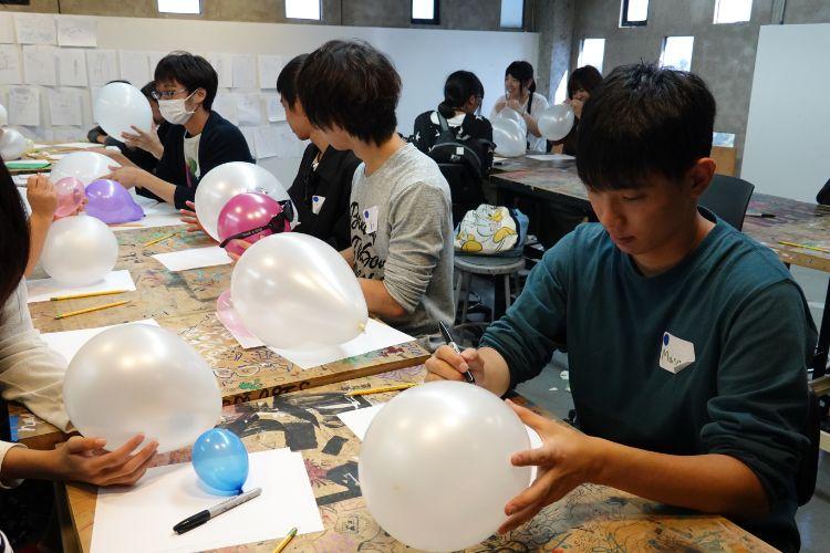 風船にマジックペンで描く学生たち