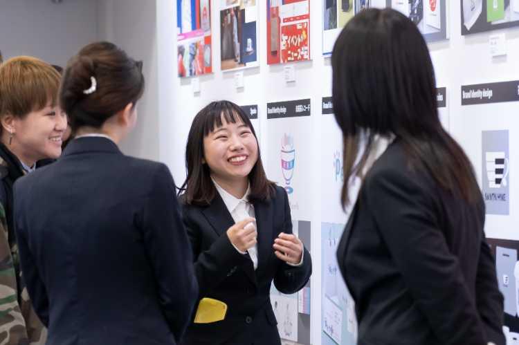作品展示会で来場者に説明を行う学生