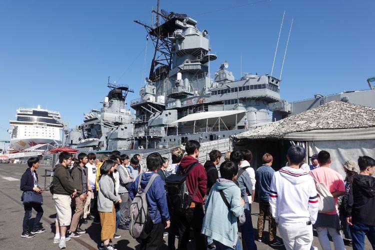 研修で戦艦と写真を撮る学生たち
