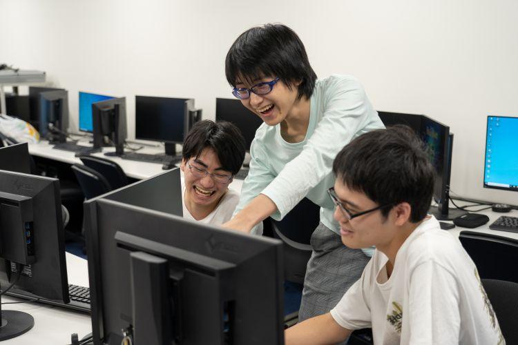 友人と楽しそうにゲーム制作に励む学生